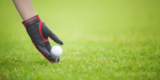 Male golf player teeing off golf ball. From tee box, wonderful cloud formation in background Stock Image
