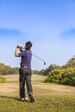 Male golf player teeing off golf ball from tee box. Wonderful cloud formation in background Royalty Free Stock Photography