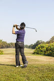 Male golf player teeing off golf ball from tee box Royalty Free Stock Photo