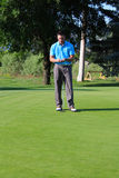 Male golfer. Young brunette golfer on the putting green Stock Image