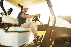 Male golfer driving a cart with golf clubs. Bag along green course Stock Photos