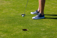 Male golfer feet next to hole royalty free stock photos