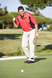 Male Golfer On Golf Course. Putting On Green Stock Image