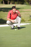Male Golfer On Golf Course. Lining Up Putt On Green Stock Photo