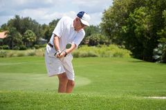 Golfer Hitting Ball. Male golfer hitting a ball on a beautiful golf course Royalty Free Stock Image