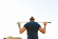 Male golfer holding driver while standing on green course. Back view of a male golfer holding driver while standing on green course Royalty Free Stock Image