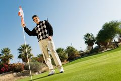Male Golfer Holding Flag And Golf Club. Full length of a young male golfer holding flag and golf club Royalty Free Stock Photography