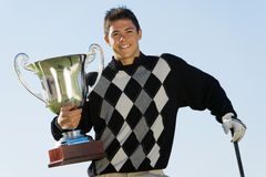Male Golfer Holding Trophy. Portrait of a happy young male golfer holding trophy against clear sky Royalty Free Stock Images