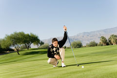 Male Golfer Lining Up Putt. Male golfer on golf course lining up putt on green Stock Photography