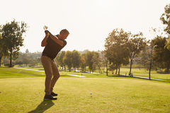 Male Golfer Lining Up Tee Shot On Golf Course Stock Photos