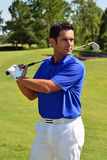 Male Golfer Poses With Golf Club. Wearing blue shirt, white pants, belt, and golf glove Stock Photo
