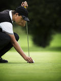 Male golfer squating at green. Royalty Free Stock Images