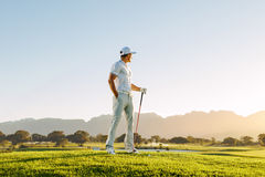 Male golfer standing on golf course Stock Photo
