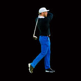 Male golfer. A male golfer swinging the club in an ending position on black background Royalty Free Stock Photo