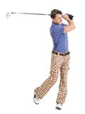 Male golfer swinging his club. Photo of a male golfer in his late twenties finishing his swing with a driver Royalty Free Stock Photo