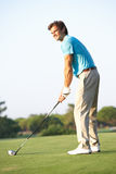 Male Golfer Teeing Off. On Golf Course royalty free stock image