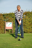 Male golfer teeing off. On the green Royalty Free Stock Photos