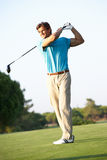 Male Golfer Teeing Off On Golf Course. Smiling royalty free stock image