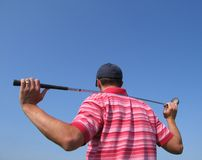 Male Golfer Tees Off. A golfer admiring his shot against a blue sky with lots of room for copy and text Stock Photo