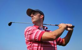 Male Golfer Tees Off. A golfer admiring his shot against a blue sky with lots of room for copy and text Stock Images
