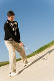 Male Golfer About To Hit Ball. Full length of a young male golfer about to hit ball out of a sand bunker Royalty Free Stock Images