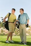 Male Golfers Carrying Golf Bags. Full length of two male golfers carrying golf bags on golf course Royalty Free Stock Photo
