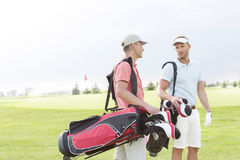 Male golfers communicating at golf course against clear sky Royalty Free Stock Photos