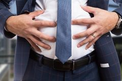 Male grabbing bloated abdomen as indigestion problem. Male grabbing bloated abdomen belly as indigestion constipation bowel or flatulence problem royalty free stock images