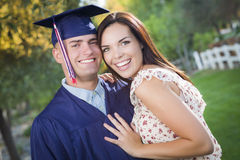 Male Graduate in Cap and Gown and Girl Celebrate Royalty Free Stock Photos