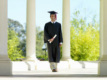 Male graduate in cap and gown smiling, portrait Royalty Free Stock Images