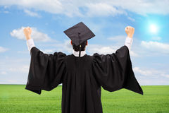 Male graduate gesturing happiness in an open field. Rear view Royalty Free Stock Photos