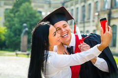 Male graduate and girl taking selfe with cellphone outside Stock Photography