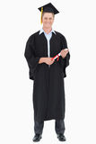 A male graduate with his degree in hand Royalty Free Stock Photography