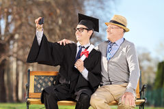 Male graduate and his father taking selfie in park. Male graduate and his father taking selfie outdoors Stock Image