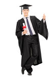 Male graduate holding diploma and giving thumb up. Isolated on white background Royalty Free Stock Photo