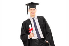Male graduate holding a diploma and leaning against a wall Royalty Free Stock Photos