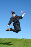 Male graduate jumping for joy. Male Graduate Leaping for Joy Outdoors Royalty Free Stock Photos