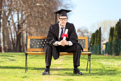 Male graduate sitting on bench and holding diploma Royalty Free Stock Photos