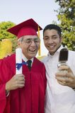 Male Graduate With Son Taking Self Portrait Stock Photography