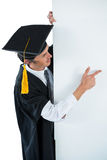 Male graduate student behind a panel and pointing with finger Stock Photos