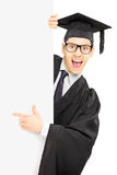 Male graduate student behind a panel and pointing with finger. Male graduate student peeking from behind a blank panel and pointing with finger isolated on white Royalty Free Stock Photos
