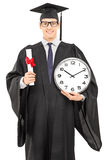 Male graduate student holding a diploma and big wall clock Stock Photo