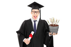 Male graduate student holding diploma and flowerpot with US doll Royalty Free Stock Images