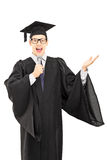 Male graduate student holding a speech on microphone Royalty Free Stock Images