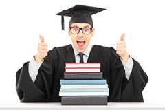 Male graduate student sitting behind books and giving thumbs up Stock Images