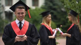 Male graduate typing message on mobile phone and smiling for camera, graduation. Stock footage stock video