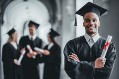 Male graduate in university. Happy female student graduate is standing in university hall in mantle with diploma in hand, smiling and looking at the camera stock photos