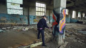 Male graffiti artist is decorating old damaged column inside empty industrial building with abstract pictures. Modern. Painter is using aerosol spray paint and stock video footage