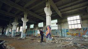 Male graffiti artist in respirator is shaking spray paint then painting on high pillar inside dirty empty building