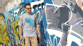 A male graffiti artist walks along a painted wall. A male graffiti artist walks near a colorful wall and throws a paint can up stock video
